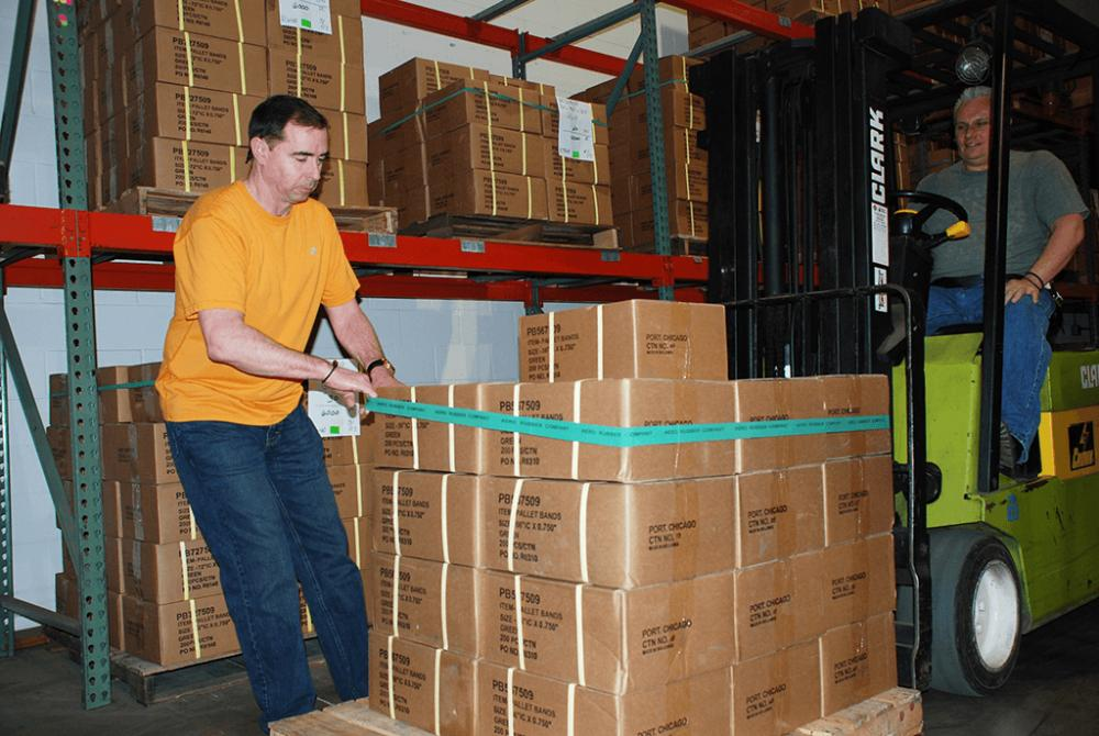 warehouse employees applying a pallet band to a pallet
